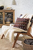 Stuhl mit Decke & gestricktem Kissen im Jacquardstil