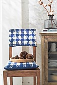 A wooden chair with a blue and white-checked knitted cushion