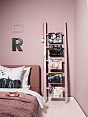 Ladder used as shelving leaning on bedroom wall
