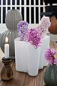 A wooden candle holder and various vases of hyacinths as table decoration