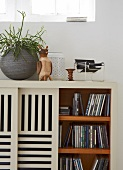 A sideboard used for storing CDs with slatted sliding doors