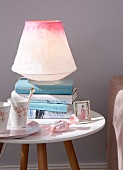 A table lamp made from coloured rice paper on a bedside table with books and porcelain cups