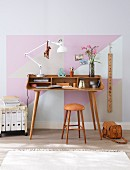 A delicate home office desk made from curved, laminated wood and a ringbinder trolley with the wall painted with pastel-coloured triangles