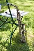A saxophone on the grass leaning against a garden chair