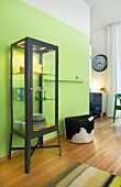 An industrial-style glass cabinet with LED lighting against a lime-green dining room wall next to a fur-covered pouffe