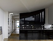 Open kitchen with high-gloss, black kitchen units in a loft-like apartment and view through an open hallway