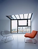 Cool design - white shell chair and red sofa in designer style in front of bank of windows with a skylight in the ceiling