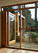 Bank of windows with wood-glass construction and open patio door with a view of a flower bed