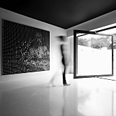 Modern painting in a minimalist room with revolving, room height window