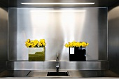 Sink in front of a wall niche clad in stainless steel and yellow flowers in vases