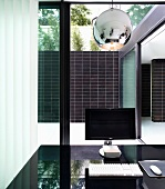 Monitor on a black table top in front of a room height bank of windows with a view of a patio with a black tiled wall