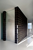 Minimalist hallway with white floor and enclosed staircase with black wall tiles