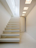 Designer staircase in white with protruding steps, above, a ceiling cut out with lights