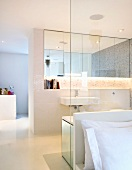 Open bathroom ensuite with a glass dividing wall to the bedroom