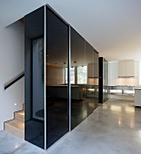 Black, high-gloss built in cupboard in the hallway in front of staircase on a polished concrete floor