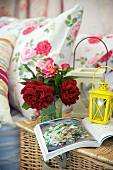 A small bunch of flowers, lanterns and a book on top of a picnic basket next to bed