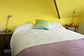 A double bed in a yellow painted attic bedroom