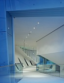 Gallery with glass balustrade and staircase in large foyer with slanting components and ceiling spotlights