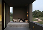 Terrace of South American house with cushions piled on concrete couch and protected by dark-grey wall elements