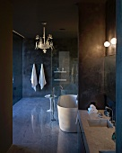 Intricate, gold pendant lamp in luxurious, dark designer bathroom with reflective floor and marble washstand