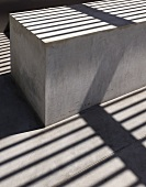 Patterns of light and shade on concrete block under wooden pergola