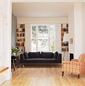 Black sofa beneath a window and antique chair with checked upholstery in an open living room
