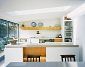 White designer kitchen with kitchen unit under a skylight in contemporary architecture