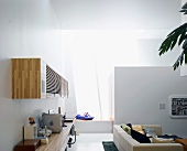 Desk and wall-mounted, wooden cupboard on a wall in a modern living room