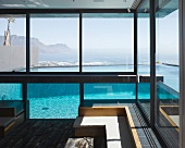Modern, minimalist living room in a contemporary home with a panoramic view of the ocean