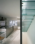 Staircase with glass stairs in an open kitchen with stainless steel kitchen unit