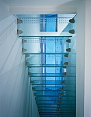 Underside view of narrow glass stairs with 'dot-like' stainless steel brackets