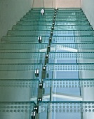 Detail of a modern stairways with glass stairs and with glue-on aluminum foil dots and stainless steel brackets