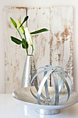 A ball made of tin strips and a lilly in a vase