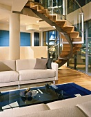 Curved staircase in a modern living room with white sectional sofa and glass coffee table
