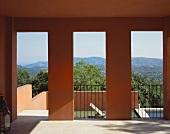 Veranda in zeitgenössischem Haus mit offenen Türausschnitten und Blick auf die Berglandschaft