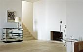 Minimalistischer Wohnraum mit Designer Spiegelkommode neben offenen Durchgang mit Treppe und Beistelltisch aus Bauhauszeit