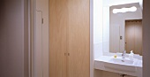 Bathroom with wooden built-in cupboard next to a simple, white wash basin