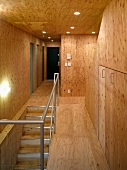 Staircase and hallway with wood paneling and ceiling