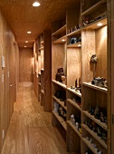 Narrow hallway with wood paneling on the wall and ceiling and built-in shelves made of wood