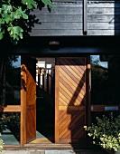 Wooden entry door with open door and view of a stairway
