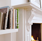 Detail of white shelves with books beside a chimney with a carved, white lacquered mantelpiece