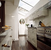 Kitchen with skylight strips above a white lacquered hanging cupboards and stainless steel oven on dark wood flooring