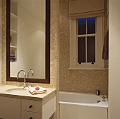 Vanity with base cabinet and drawer in front of a tall mirror on a tiled dividing wall in front of a bathtub