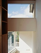 Open room with view of a window on the diagonal and return wall with skylight