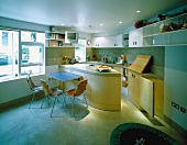 Open kitchen with modern built-in, curved counter and dining area with chairs