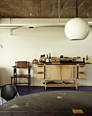 Spherical hanging lamp in retro style and old wooden work bench on the wall