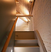 Detail of ascending stairs into an attic with whitewashed brick wall