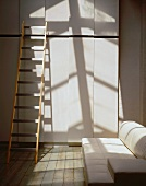Ladder in front of a contemporary built-in cupboard and white leather couch