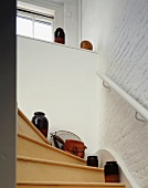 Detail of ascending stairs with terra-cotta containers on wooden stairs and whitewashed brick wall