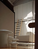 Multi-piece side table set and ladder resting on a white, designer built in cupboard